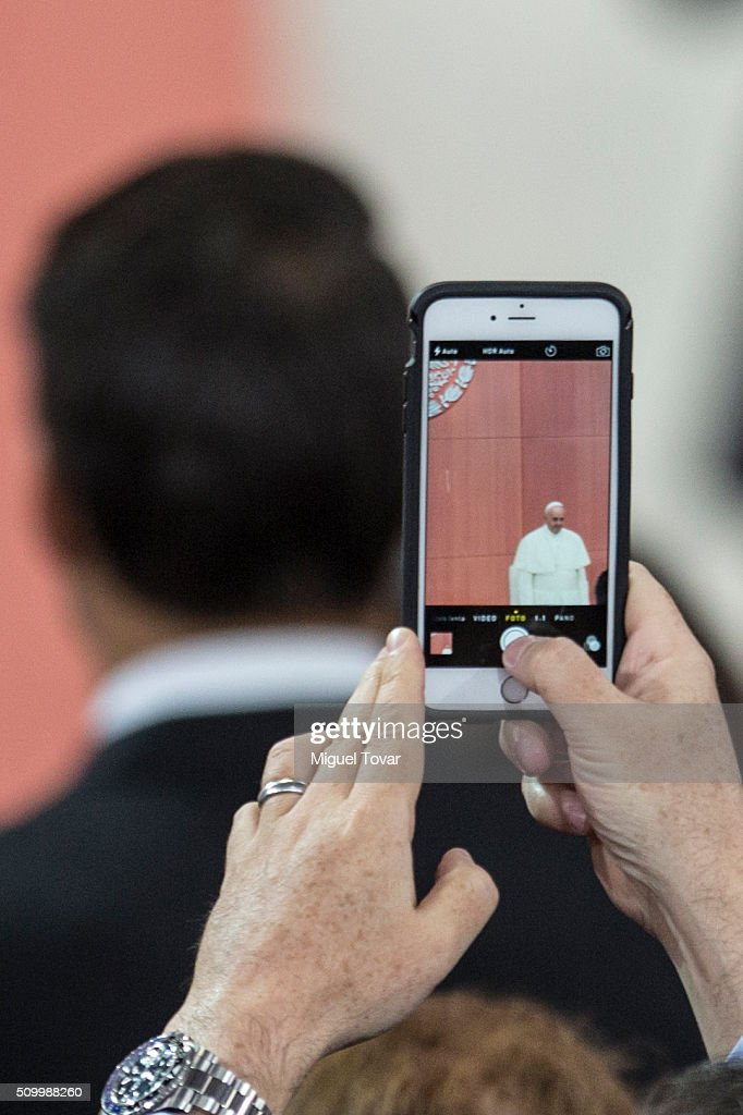 A man takes pictures of Pope Francis during the welcome ceremony at Palacio Nacional on February 13, 2016 in Mexico City, Mexico. Pope Francis will be on a five days visit in Mexico from February 12 to 17 where he is expected to visit five states.