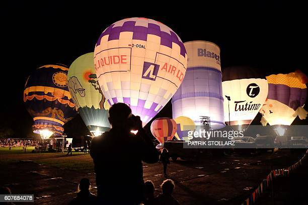 A man takes pictures of the balloon nightglow as participants of the 60th Coupe Aeronautique Gordon Bennett World Long Distance Gas Balloon...