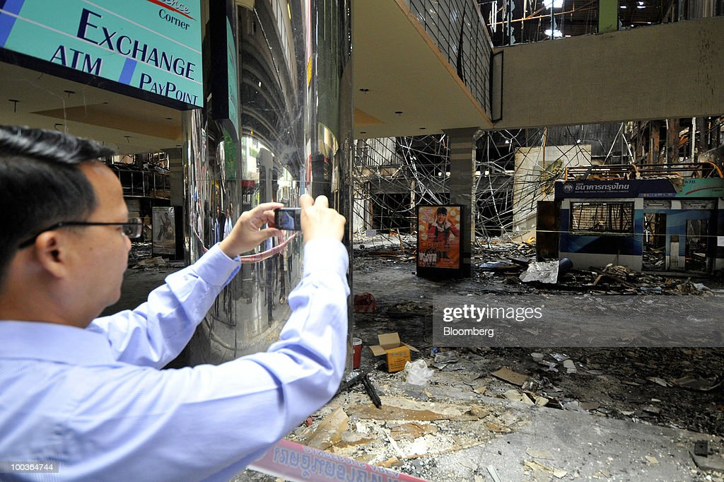 A man takes pictures of the burned remains of the Siam Cinema at the Siam Square shopping area in Bangkok, Thailand, on Monday, May 24, 2010. Efforts to clean up the city's commercial district gathered pace after the area was torched by rioting anti-government protesters. Photographer: Udo Weitz/Bloomberg via Getty Images