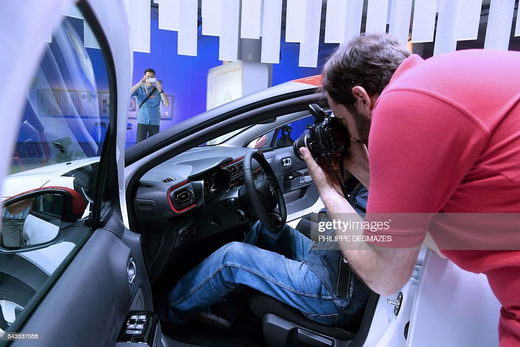 A man takes pictures of the new Citroen C3 of French automobile manufacturer, during its presentation in Lyon on June 29, 2016. / AFP / PHILIPPE