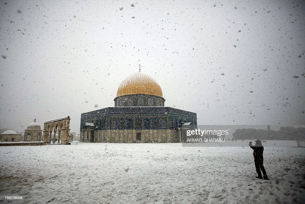 A man takes pictures of the snow-covered Dome of the Rock at the Al-Aqsa mosque compound in the old city of Jerusalem on January 10, 2013. Jerusalem was transformed into a winter wonderland after heavy overnight snowfall turned the Holy City and much of the region white, bringing hordes of excited children onto the streets. AFP PHOTO/AHMAD GHARABLI