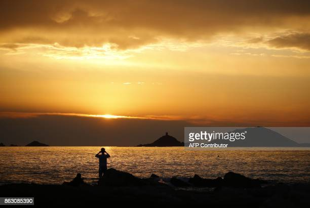 A man takes pictures of the sunset over the Sanguinaires Islands in Ajaccio on the French Mediterranean Island of Corsica on October 19 2017 / AFP...
