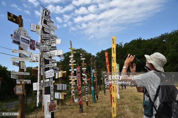 A man takes pictures of totems bearing various slogans during a twoday meeting organised by opponents to a controversial international airport...