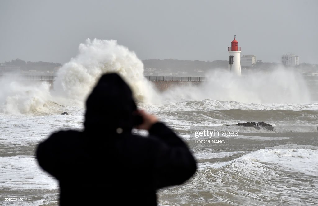A man takes pictures of waves breaking against a pier in Les Sables-d'Olonne, western France, on February 9, 2016. High winds buffeted northwestern Europe on February 8, leaving one woman in France in a coma after she was hit by an advertising hoarding. Electricity was cut to 5,000 homes in northern France. / AFP / LOIC VENANCE