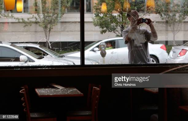A man takes pictures through a broken window at a Boston Market fast food restaurant after antiG20 Summit protestors smashed its windows September 24...