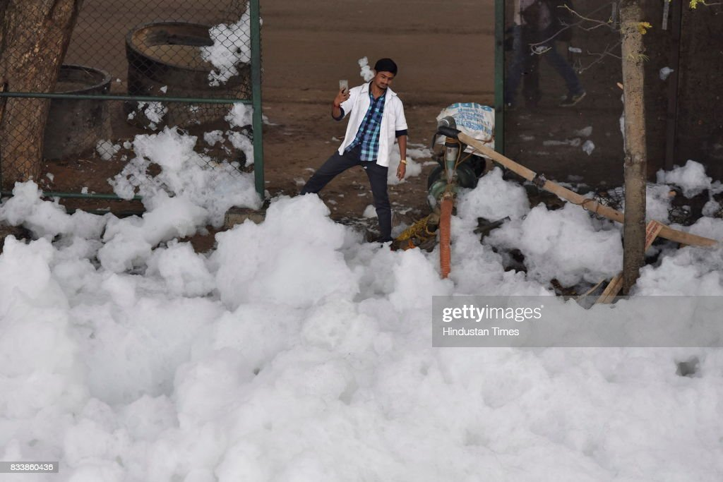 A man takes selfie against the pile of froth coming from the Bellandur Lake on August 17, 2017 in Bengaluru, India. Rapid urbanisation is taking its toll, between 2001 and 2011, the city's population increased from 6.5 million to 9.6 million, the highest rate of growth of any city in India. The indiscriminate discharge of household waste and industrial effluents into lakes is what causes the toxicity, leading to the water body foaming. According to a report by the Karnataka State Pollution Control Board, of the 67 lakes surveyed in Bengaluru, none had water that was fit for drinking.