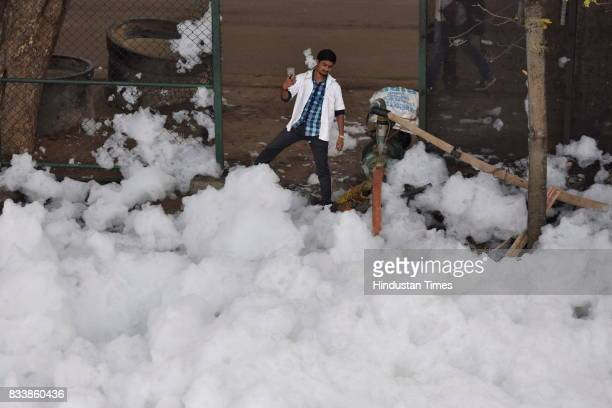 A man takes selfie against the pile of froth coming from the Bellandur Lake on August 17 2017 in Bengaluru India Rapid urbanisation is taking its...