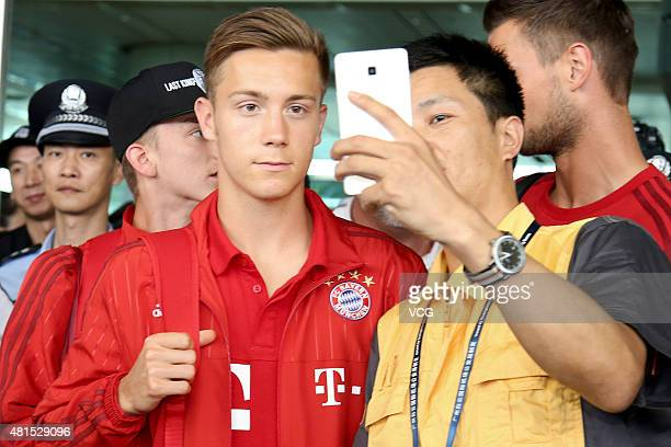 A man takes selfies with Sinan Kurt of FC Bayern Muenchen at airport on July 22 2015 in Guangzhou China