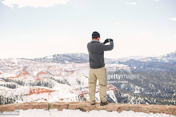 Man takes smart phone picture above Bryce Canyon