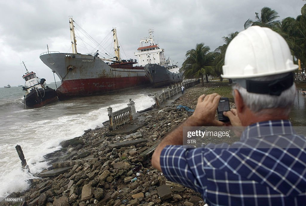 A man takes snapshots of a cargo ship stranded on the shore of Colon city on the Atlantic Ocean, on March 4, 2013. Six cargo ships run aground following heavy rains, winds and huge waves due to a cold front from the north on the Panama Caribbean.