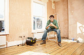 Man Taking a Break While Renovating Room