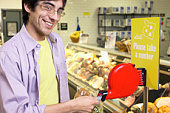 Man taking a number at delicatessen