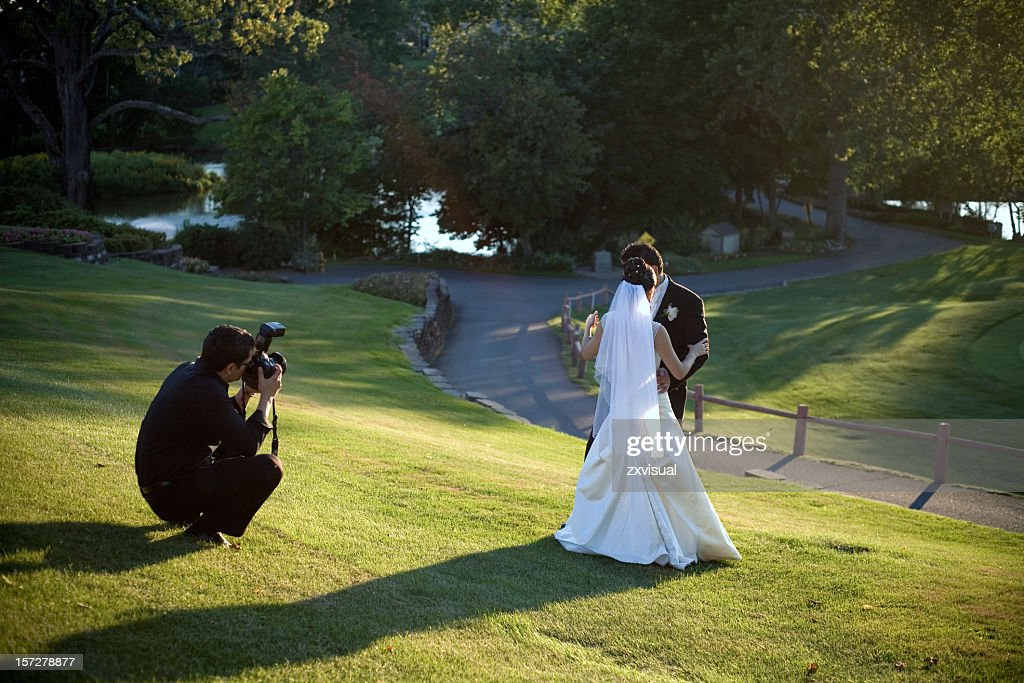 A man taking a photo of a bride and groom missing in grass : Stock Photo