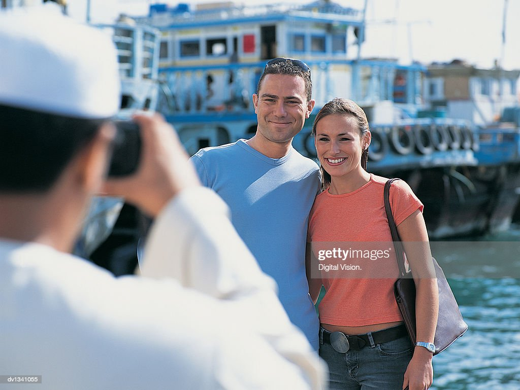 Man Taking a Photo of a Couple on Holiday Standing By the Dubai Creek, Dubai