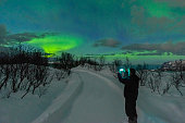 Man taking a picture of the Northern Lights, polar light or Aurora Borealis in the night sky over Senja island in Northern Norway. Snow covered mountains in the background with water of the Norwegian
