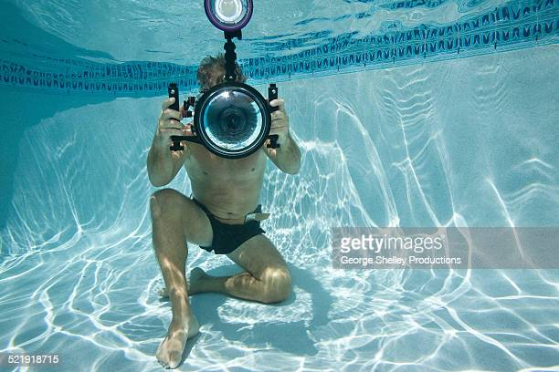 Man taking a picture underwater in swimming pool