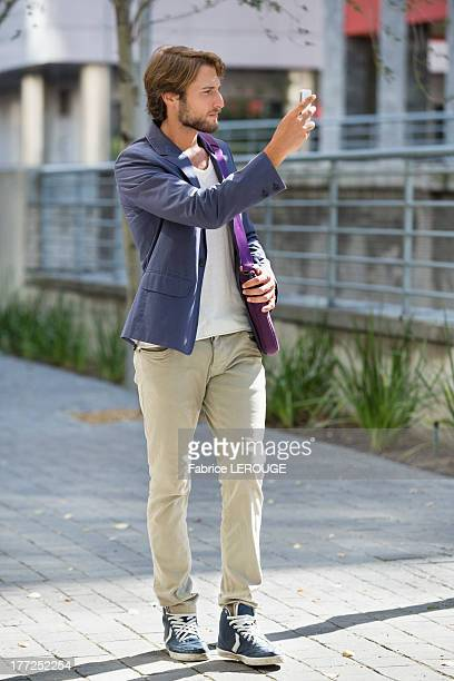 Man taking a picture with mobile phone on a street