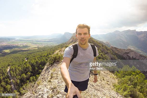 Man taking a selfie on the top of mountain.