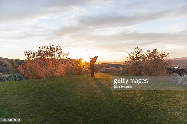 A man taking a shot off a golf tee on a golf course into the sunset.