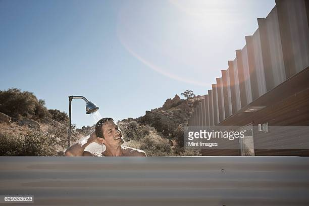 A man taking a shower outdoors on the terrace of a low impact eco house.
