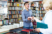 Positive man taking new book from seller in book store