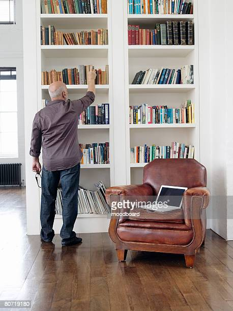 Man Taking Book Out of Shelf