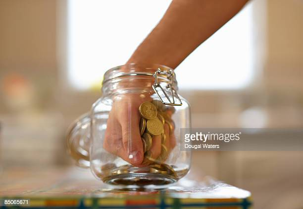 Man taking coins out of jar.