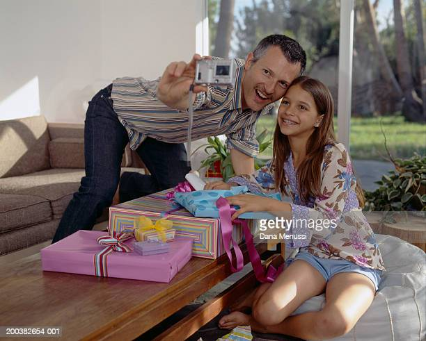 Man taking digital photo of himself and daughter (9-11) with presents