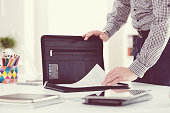 Man taking documents from briefcase in an office. Close up of hands, unrecognizable person.
