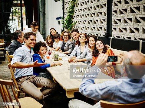 Man taking family portrait in restaurant