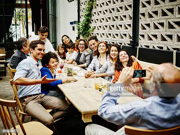 Man taking family portrait in restaurant