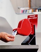 Man taking first ticket from dispenser, close-up