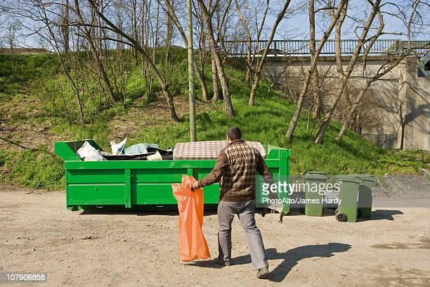Man taking garbage to dumpster