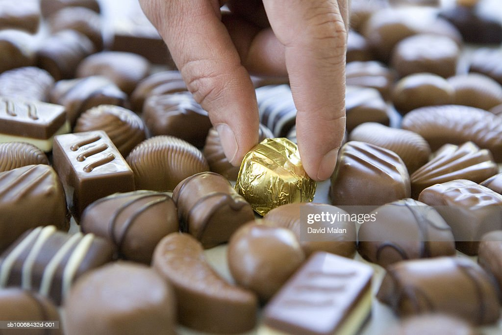 Man taking gold covered chocolate from pile of uncovered ones : Stock Photo