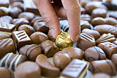 Man taking gold covered chocolate from pile of uncovered ones