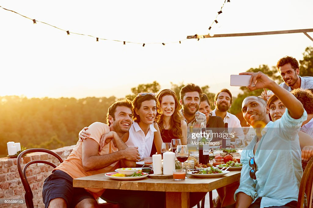 Man taking group selfie on mobile phone at party : Stock Photo