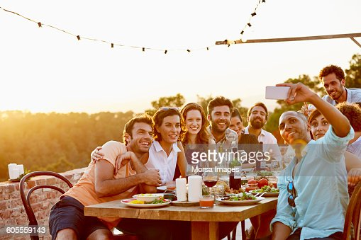 Man taking group selfie on mobile phone at party