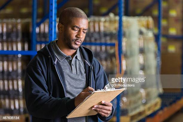 Man taking inventory of charity food donations in warehouse