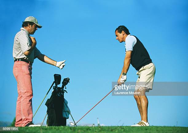Man taking lessons with golf instructor