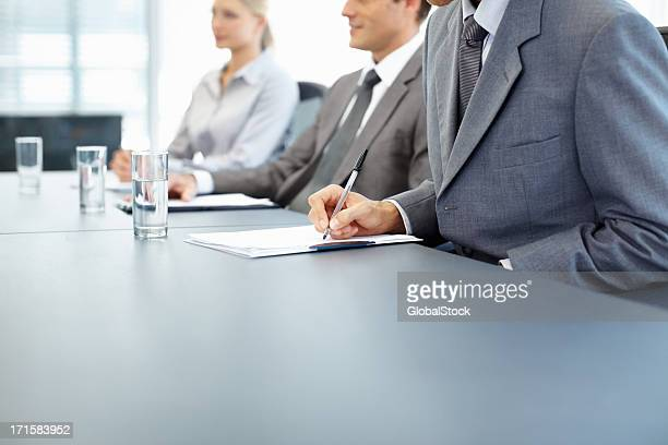 Man taking notes during business presentation