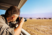 Man taking photo of herd of elephants during Great Migration from safari jeep, Kenya, Africa