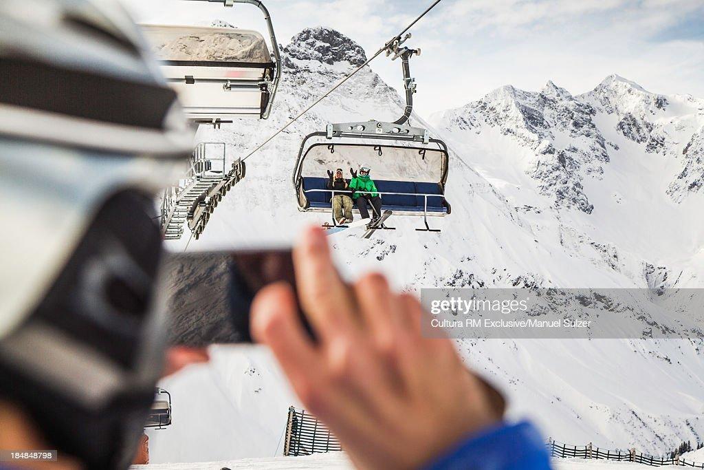 Man taking photo of friends on ski lift, Warth, Vorarlberg, Austria : Stock Photo