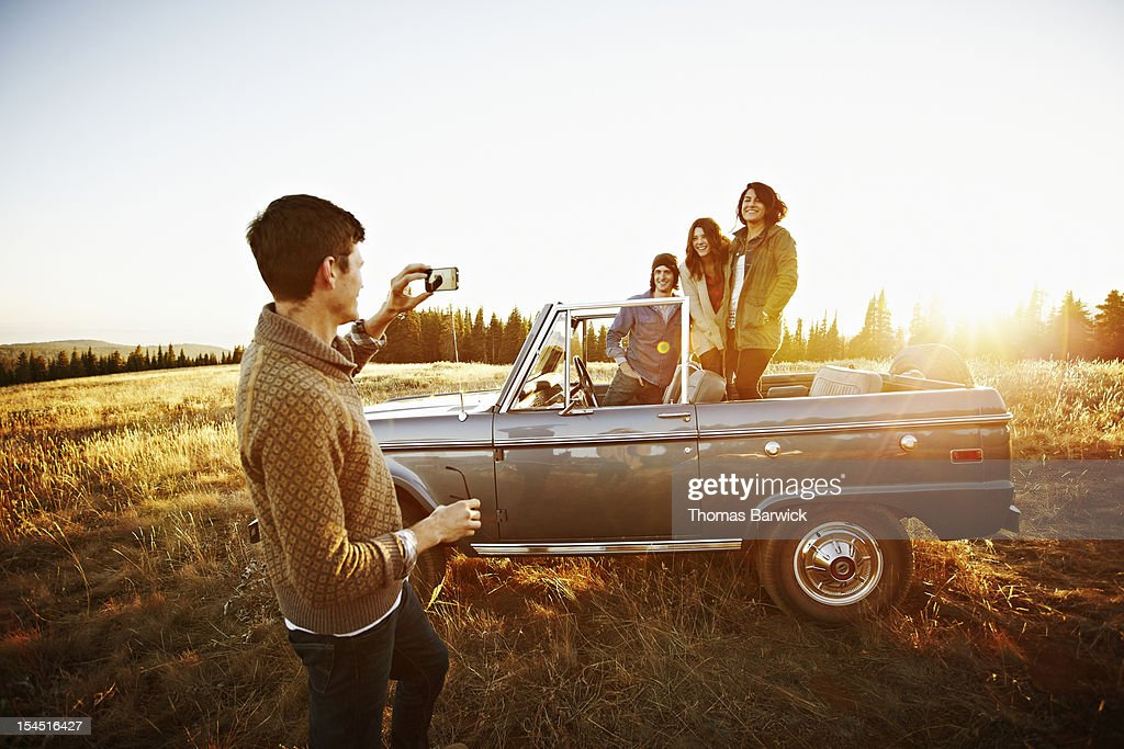 Man taking photo of friends with smartphone