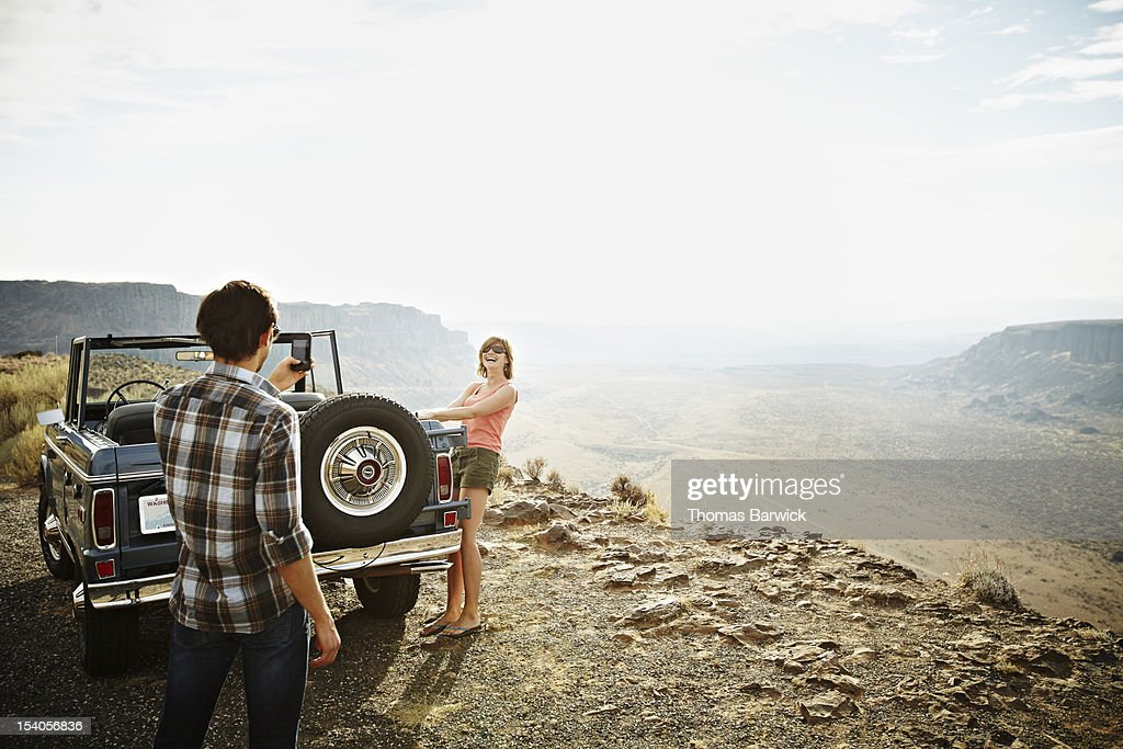 Man taking photo of girlfriend with smartphone : Stock Photo