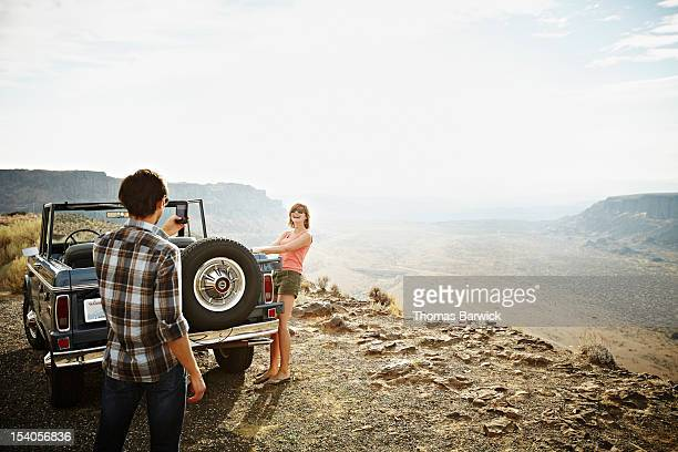 Man taking photo of girlfriend with smartphone