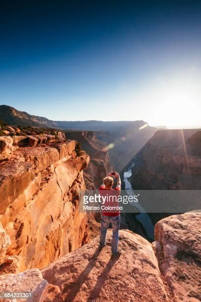 Man taking photo of Grand Canyon at sunrise