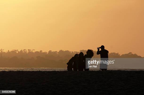Man taking photo of group of girls with his smart phone in Monterey beach at sunset