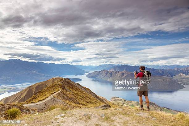 Man taking photo of scenic landscape, New Zealand