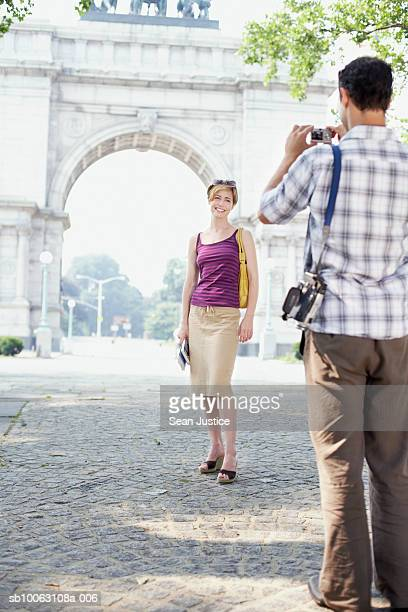 Man taking photo of woman in front of monument