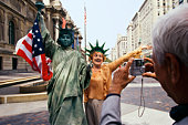 Man taking photo of woman with Statue of Liberty replica